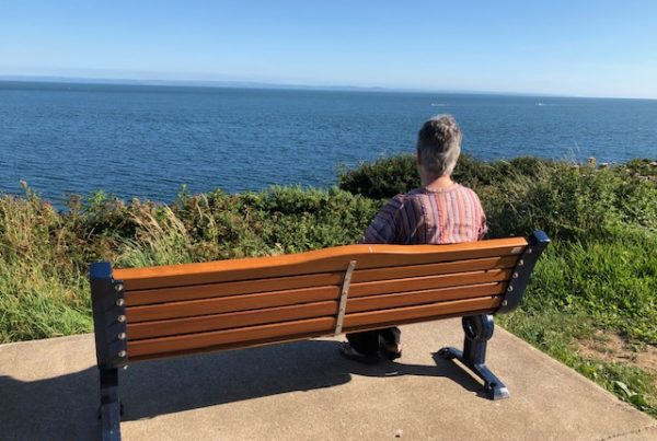 person on bench looking out to sea